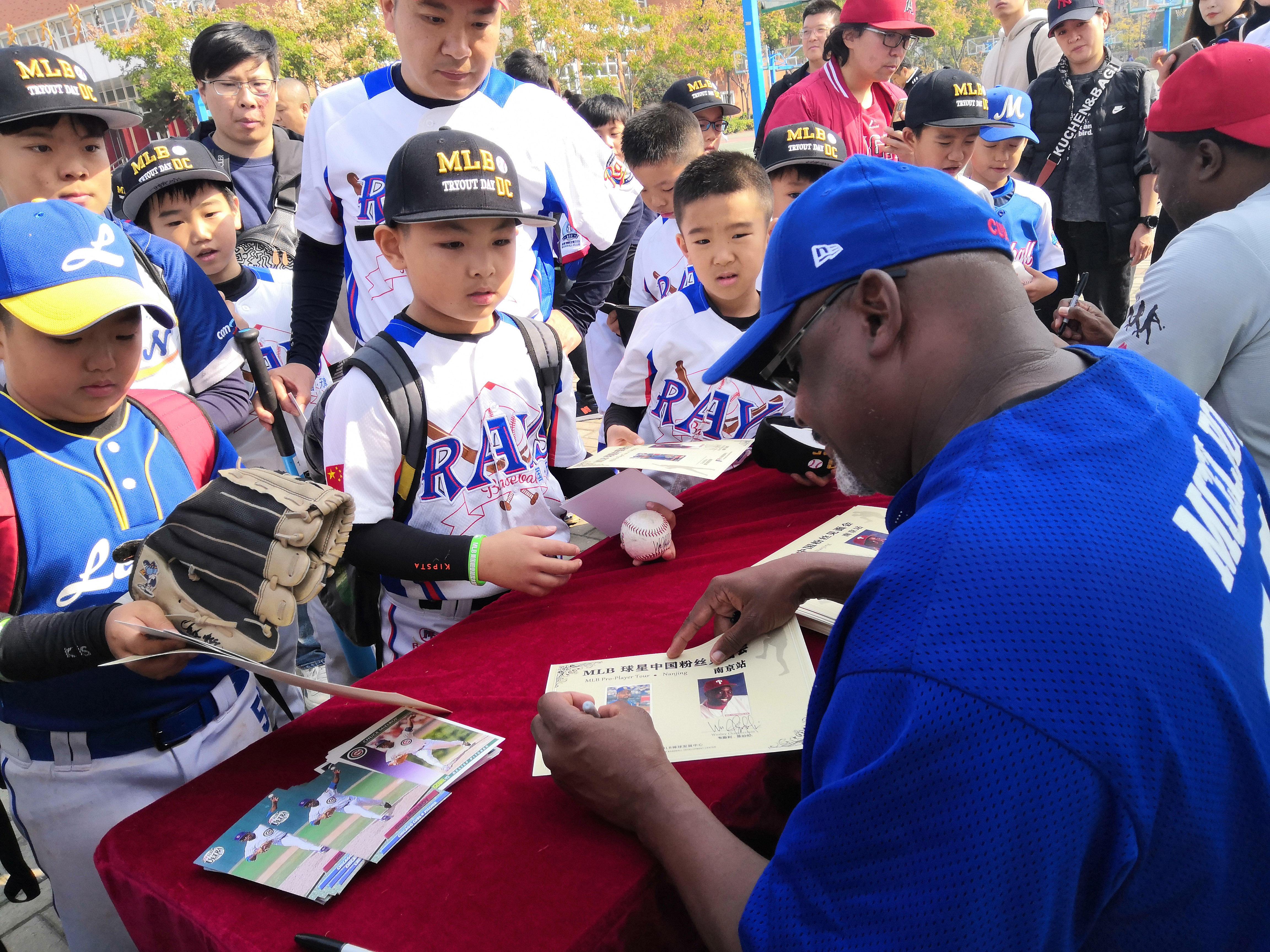 两位前美职棒大联盟球员正在给小选手签名